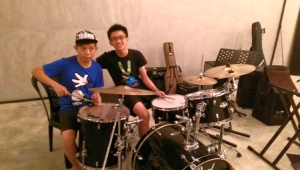 Wei Ze (right), a bassist on our worship team, started out learning the drums in our School of Worship. Here, he is offering tips to the Malaysian drummer, Wei Jie, who is debuting on their worship team.