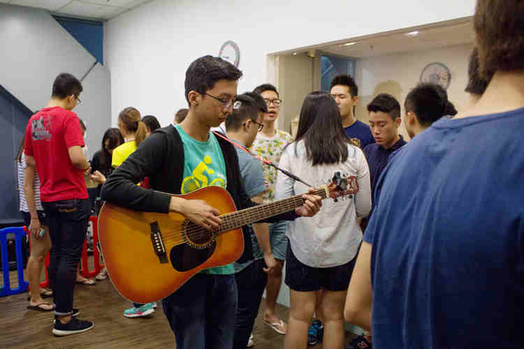 Creating the atmosphere: One of our leaders, Ming Rong, playing the guitar during the Pre-BMI prayer
